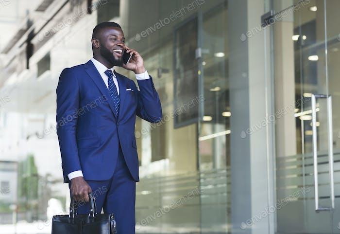 Cheerful Businessman Having Phone Conversation Next To Office Building
