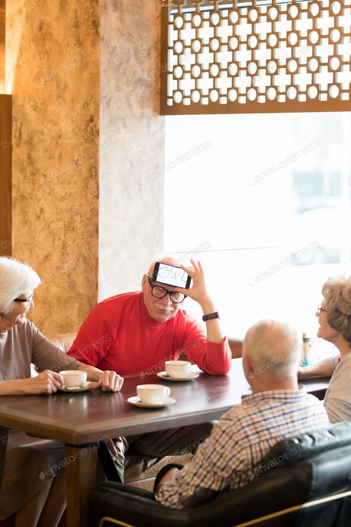 Elderly friends playing charades in cafe