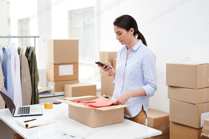 Young mobile female with smartphone taking photo of folded pullover in open box
