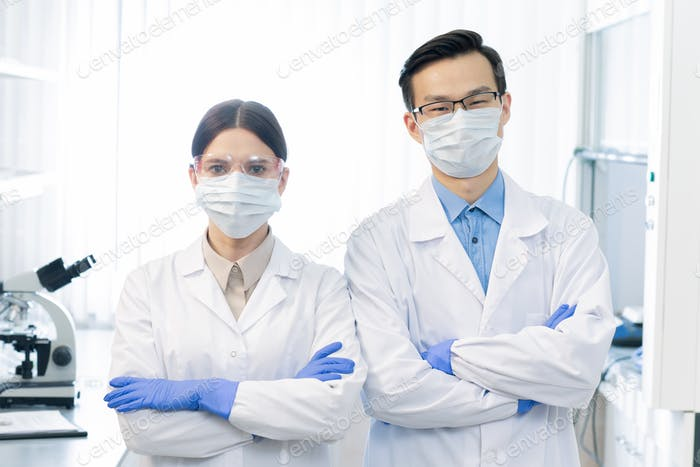 Two young masked intercultural scientists in whitecoats and gloves