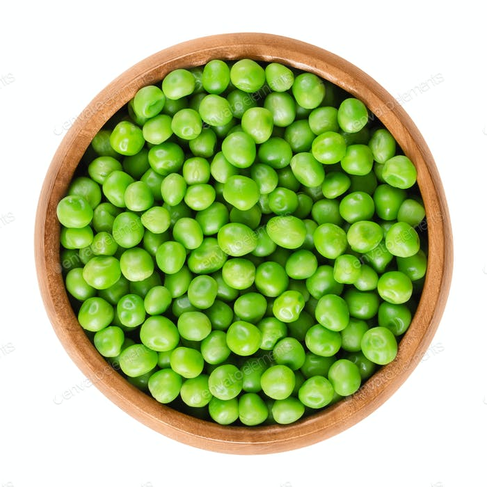Raw peas in wooden bowl over white
