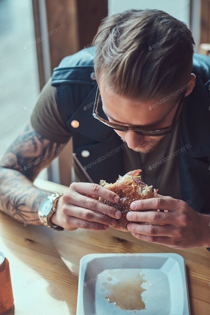 Handsome hipster sits at a table, decided to dine at a roadside cafe, eating a hamburger.