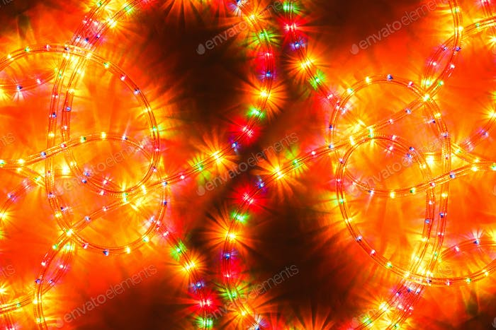 Colored light christmas garland illumination background, unfocused.