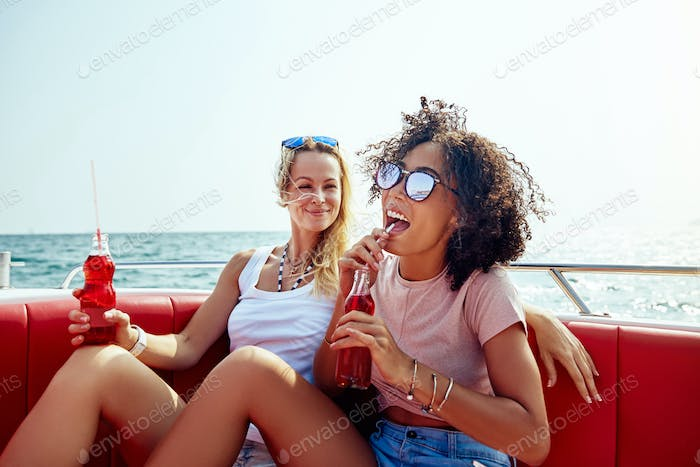Two friends laughing and having drinks on a boat