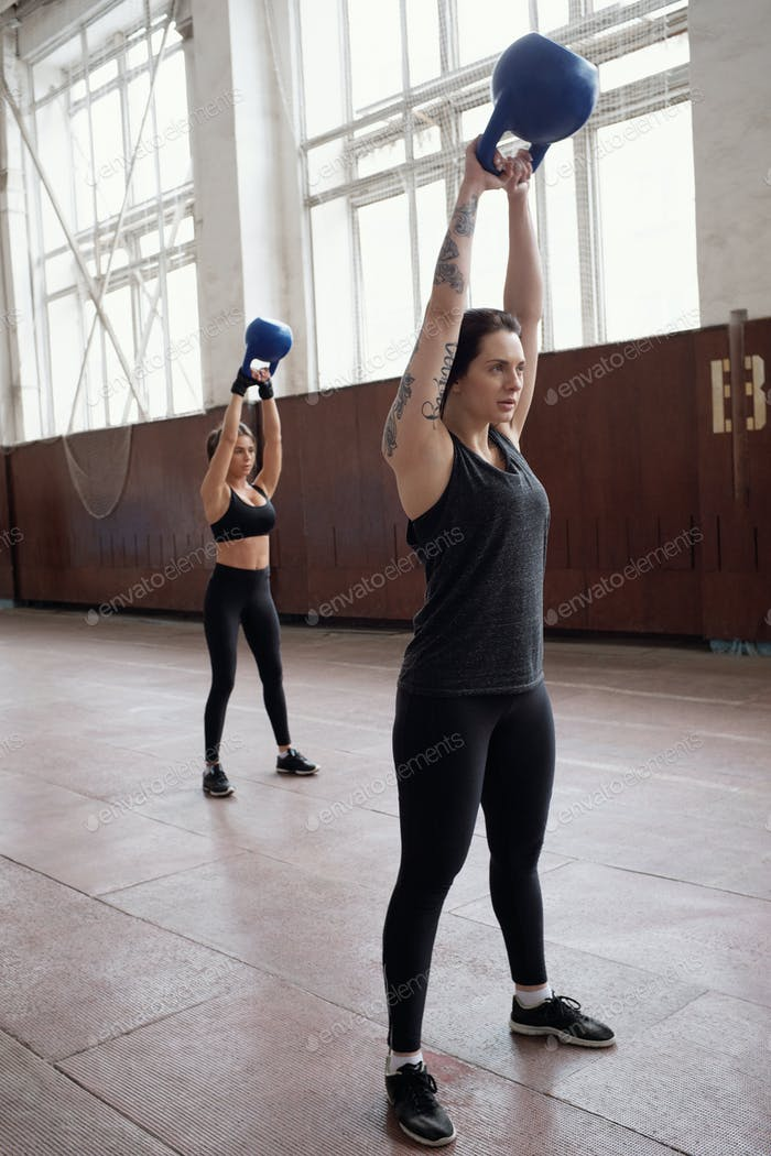 Young Caucasian women in black activewear working out with kettlebells