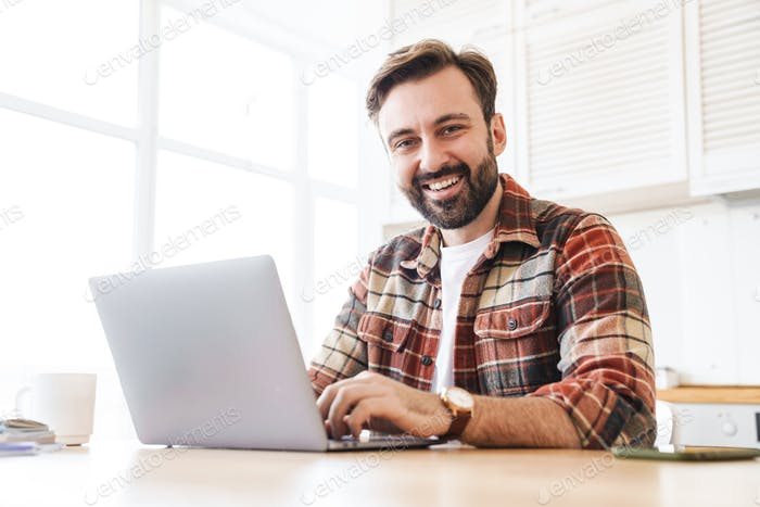 Portrait of man working with laptop and laughing while sitting at table