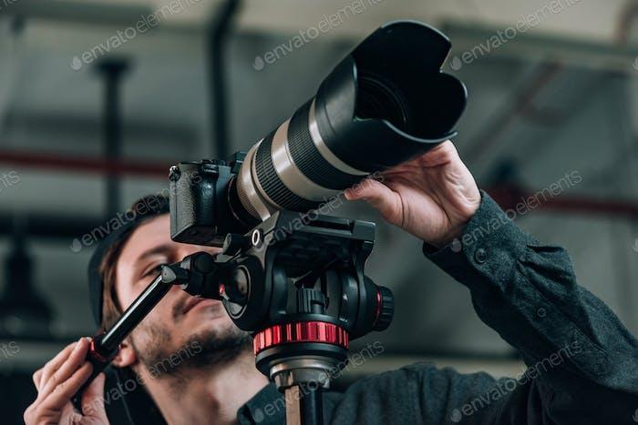 Low angle view of cameraman looking at camera display