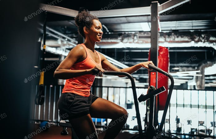 Beautiful fit woman training by riding a bicycle in a gym