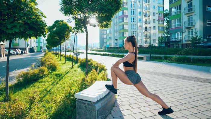 Flexible Frau Stretching Beine auf Bank im Freien