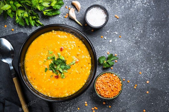 Red lentil soup on black top view