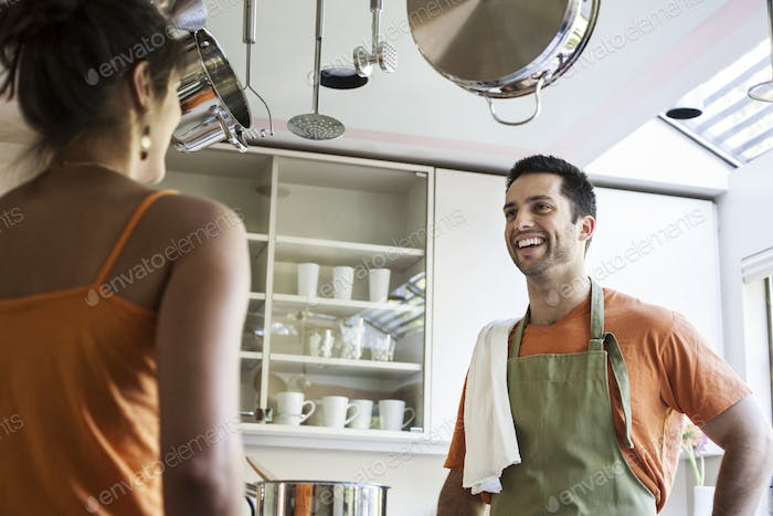 HIspanic couple at home in their kitchen.