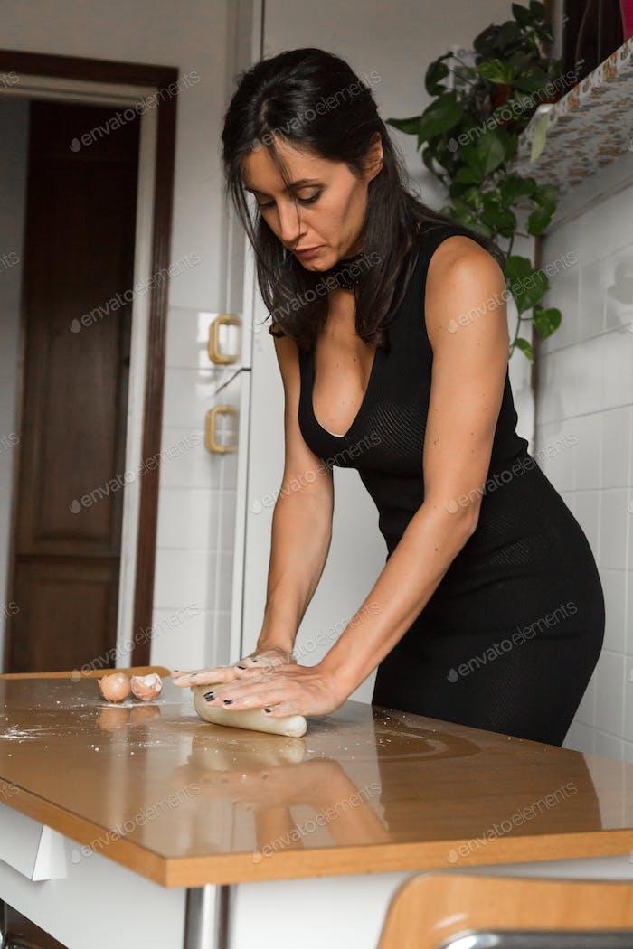 Beautiful young brunette preparing homemade fresh pasta