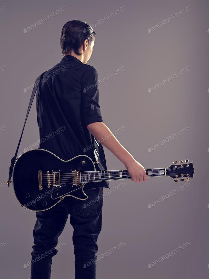Gitarrist mit schwarzer E-Gitarre. Rückansicht