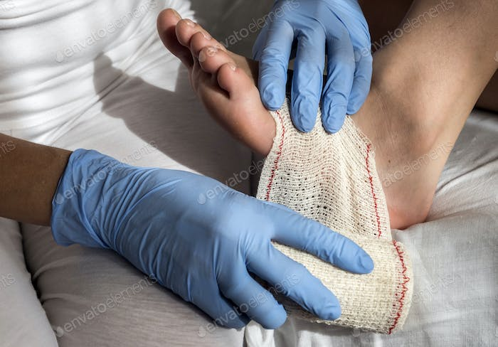 Close-up Of A Nurse Tying Bandage On Patient's Foot