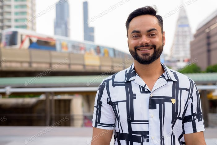 Happy young bearded Indian man smiling against view of train at sky train station