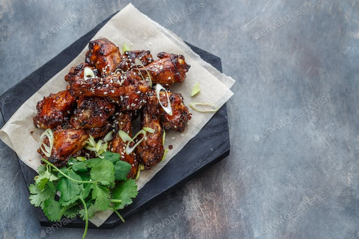 Baked chicken wings with sesame and sauce. Food background with copy space. Top view.
