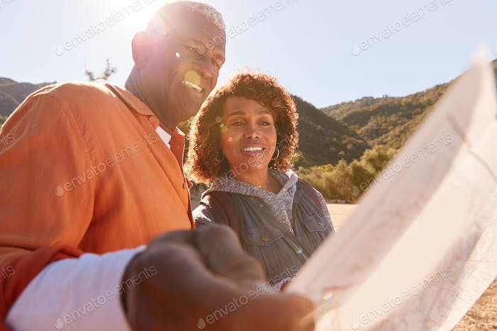 Senior Couple Looking At Map As They Hike Along Trail In Countryside Together