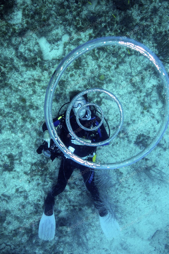 Scuba diver blows bubble rings which rise to the surface.