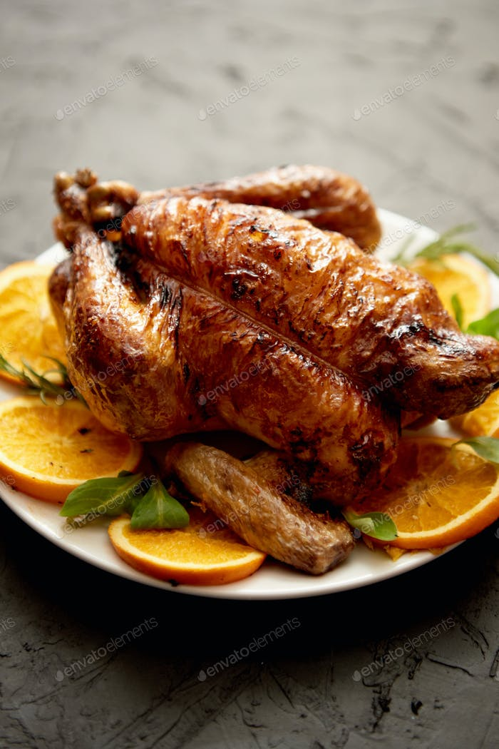 Roasted whole chicken or turkey served in white ceramic plate with oranges