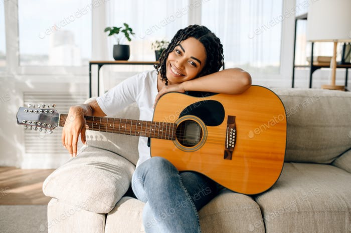 Happy woman with guitar sitting on sofa at home