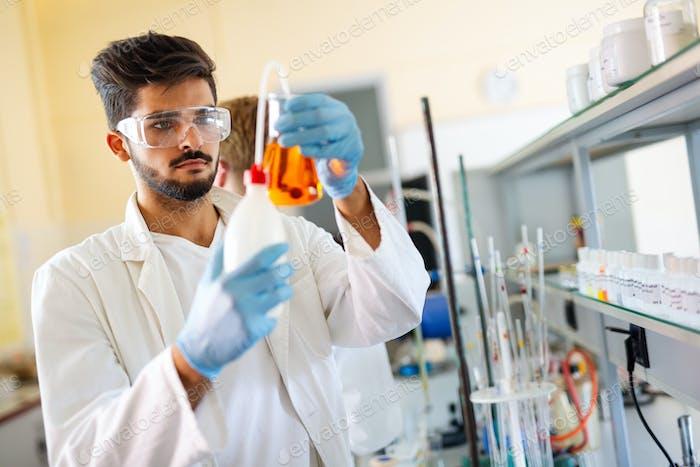 Forschungswissenschaftler mit Blick auf Reaktion im Reagenzglas im Labor