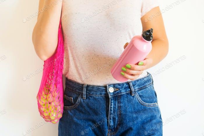 Woman with reusable mesh bag and bottles