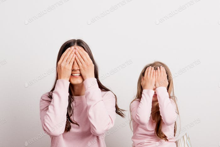 A small girl and her mother in a studio, hands on their eyes.
