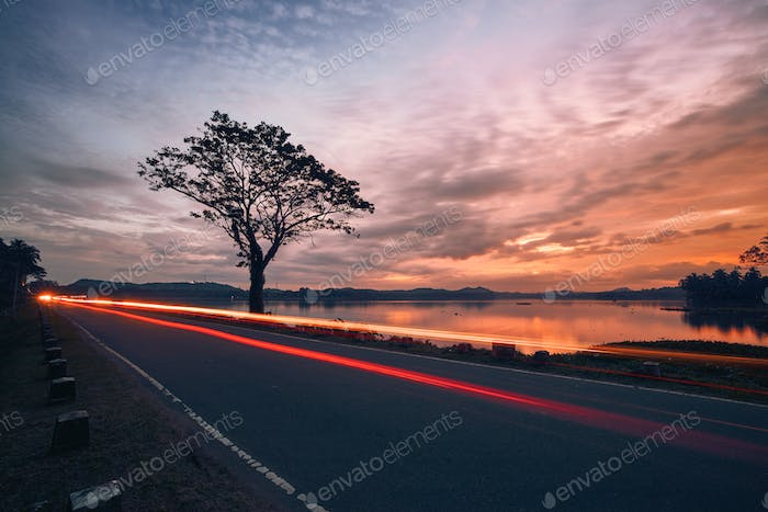 Light trails of car on road at sunset