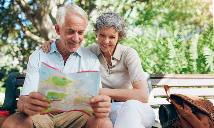 Happy mature couple using city map for direction
