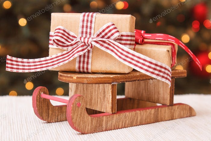 Wrapped Gift On Wooden Sled And Christmas Tree With Lights In