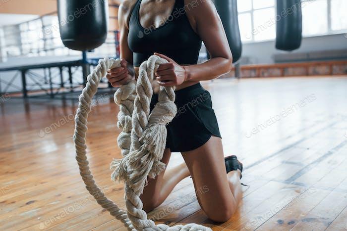 Zugeschnittene Fotos. Blonde Sport Frau haben Übung mit Seilen in der Turnhalle. Starke Weibchen