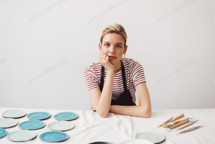 Pretty girl in black apron sitting at the table with handmade plates and dreamily looking in camera