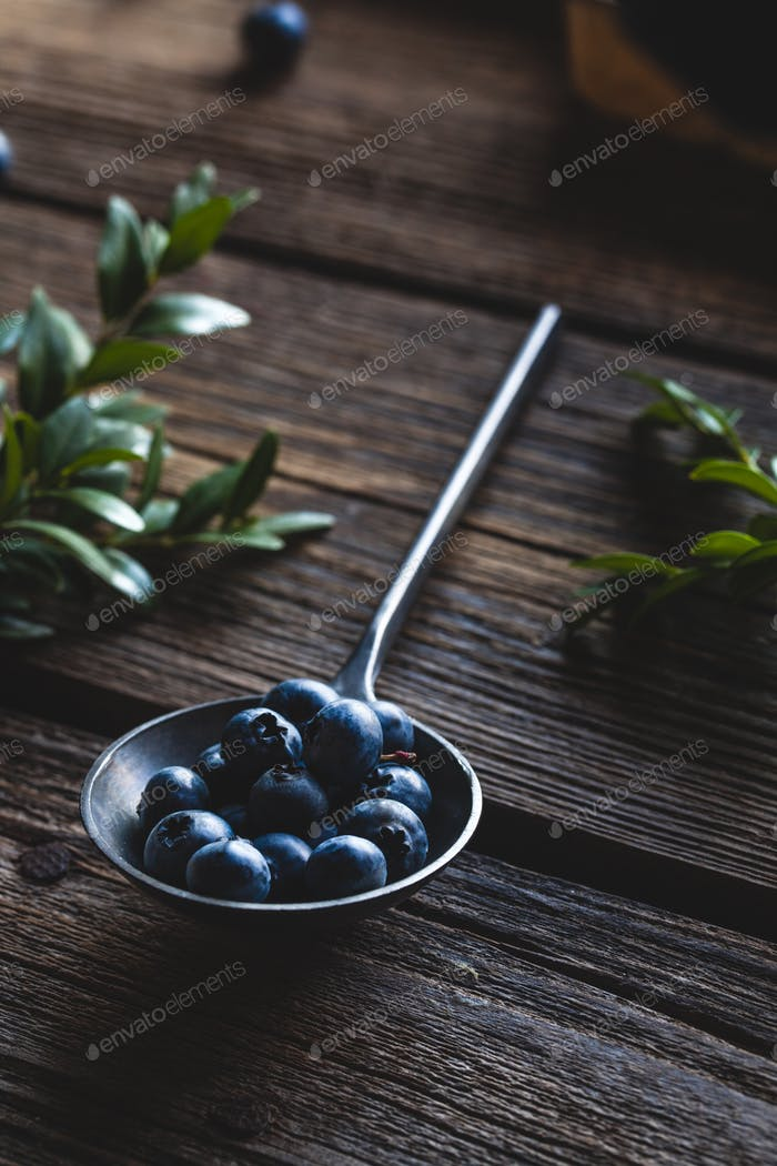 Blueberry in spoon on wooden table background. Blueberries close up. Healthy food, health