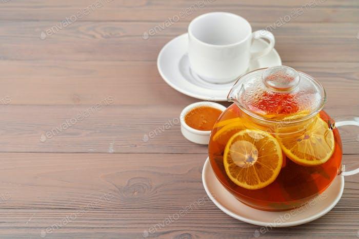 Glasteekanne mit schwarzem Tee und Zitrusfrüchten