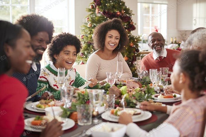 Happy multi generation mixed race family sitting at their Christmas dinner table, talking