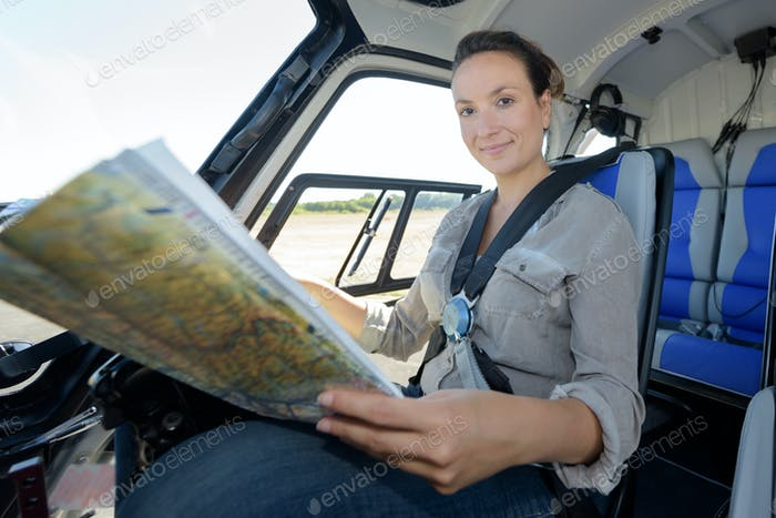 female pilot in cockpit of a helicopter with aviation map