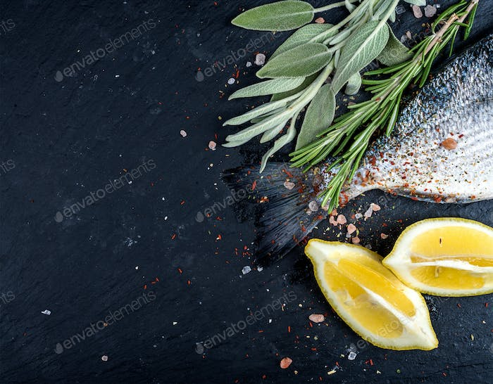 Tail of fresh raw Dorado or sea bream fish on black slate stone board