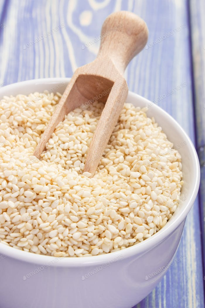 Sesame seeds with wooden scoop in white bowl