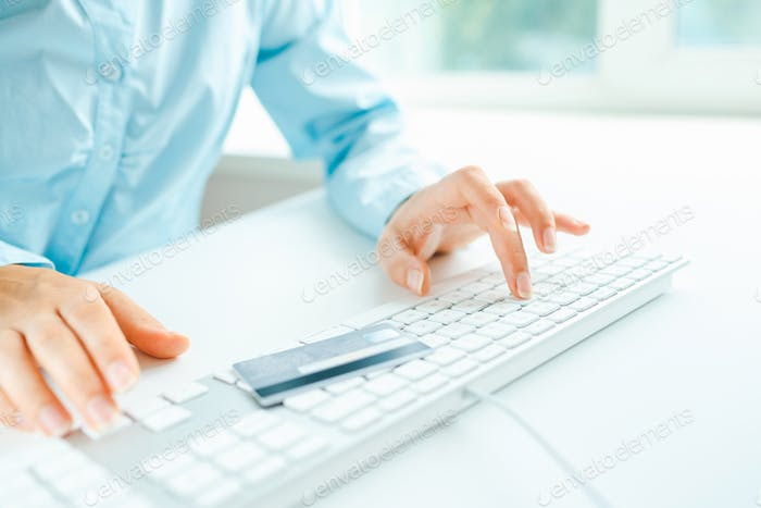 Hands using computer and credit card on it
