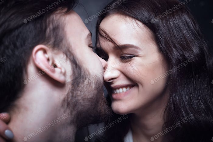 Beautiful cute loving couple in a studio with dark walls