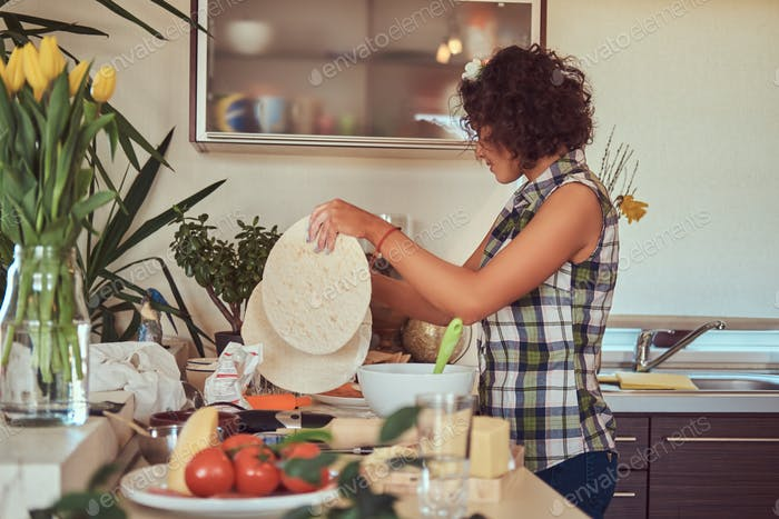 Charming curly Hispanic girl cooking in her kitchen.