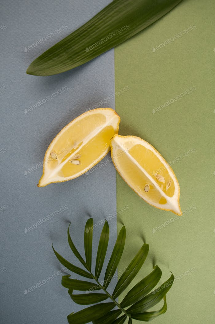 Composition with two slices of limonoma and green leaves on a bl