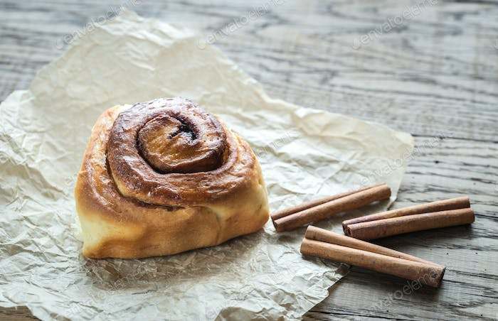 Cinnamon roll on the wooden background