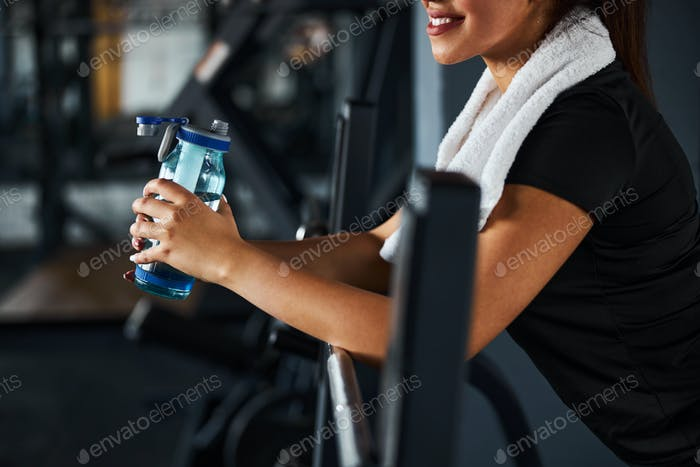 Cheerful young woman quenching thirst in gym