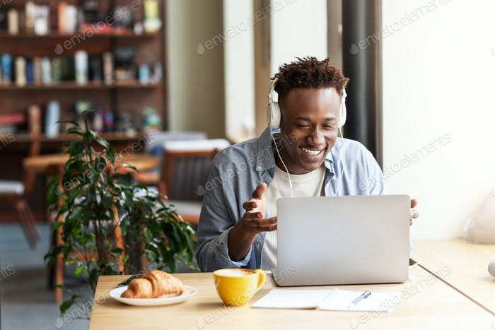 Happy black guy in headphones communicating online from laptop computer at coffee shop, copy space