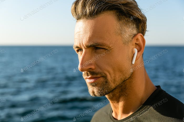 close-up portrait of attractive adult man with wireless earphones on seashore
