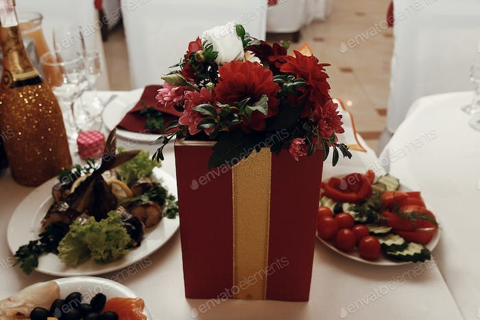 stylish red vase with flowers on table