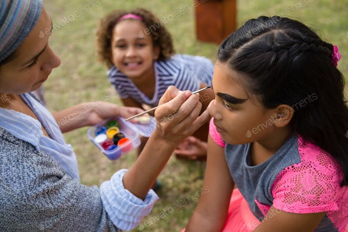 Woman doing face paint to girl
