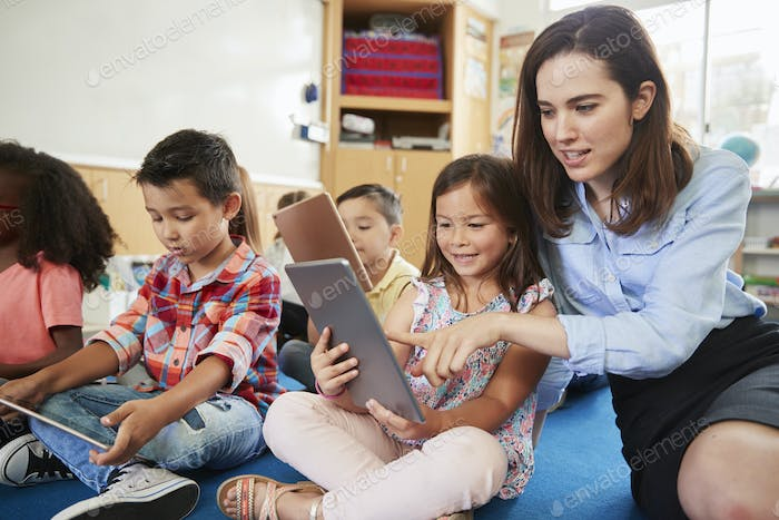 Teacher helps girl in elementary class with tablet computers