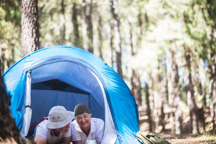 Happy retired senior caucasian couple enjoying the outdoor leisure activity together in tent camping